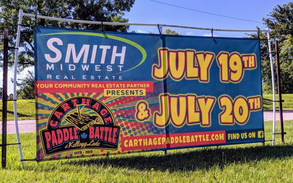 Smith Midwest Real Estate, your community real estate partner presents: Carthage Paddle Battl at Kellogg Lake. Estd 2019. July 19th & July 20th. carthagepaddlebattle.com.  Find us on facebook. Logo and banner designed and printed by netfishes of Carthage, MO.